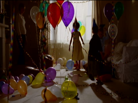 young children wearing party hats dance in a living room decorated with balloons and streamers at a birthday party - 30 34 years stock videos and b-roll footage