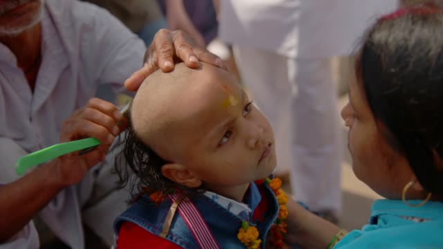 Young child's hair is shaved, Varanasi, India