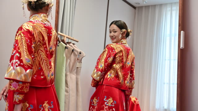 young chinese bride looking at her reflection in mirror - traditional clothing stock videos & royalty-free footage