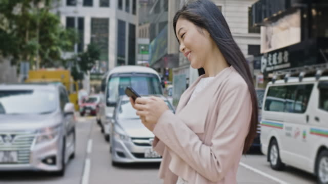 Young Chinese business woman crossing street while checking her mobile phone