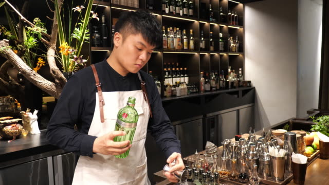 Young Chinese cocktail master shaking cocktail in night bar.