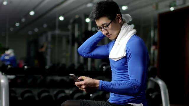 junge chinesen mit handy im modernen fitnessraum - sportkleidung stock-videos und b-roll-filmmaterial