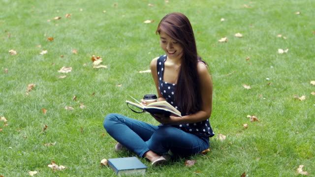 stockvideo's en b-roll-footage met jonge chinese student studies in het park (slow motion) - natuurlijk haar