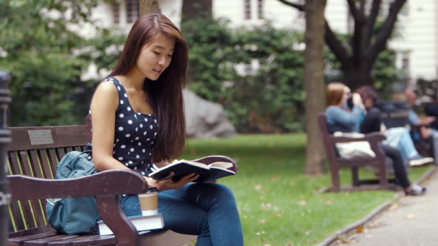 Young Chinese Student studies in the park (slow motion)