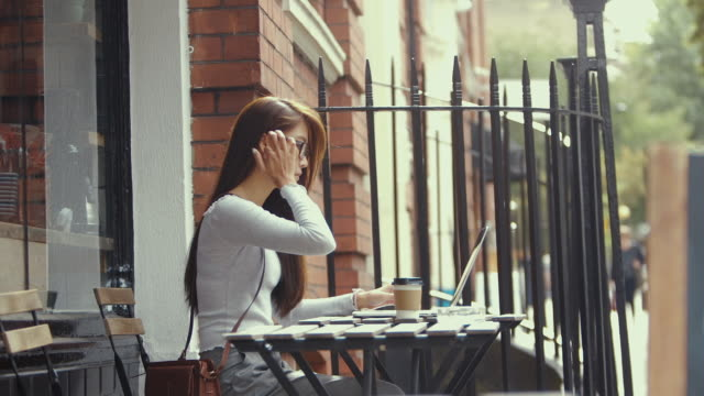 young chinese student using laptop in cafe (slow motion) - studentessa di scuola secondaria video stock e b–roll