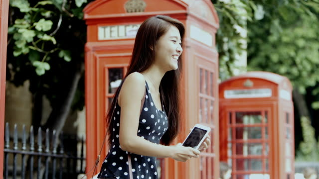 young chinese tourist takes a selfie in london (slow motion) - telephone booth stock videos & royalty-free footage