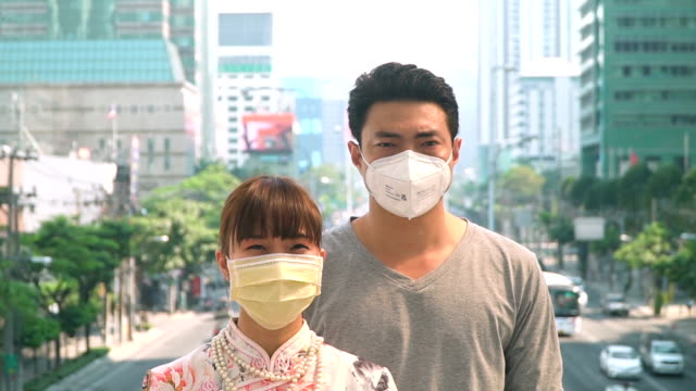 young chinese woman and boyfriend wearing mask looking at camera in the foggy city - protective mask workwear stock videos and b-roll footage