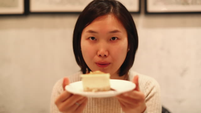 young chinese woman enjoying a slice of cake - altruismo video stock e b–roll