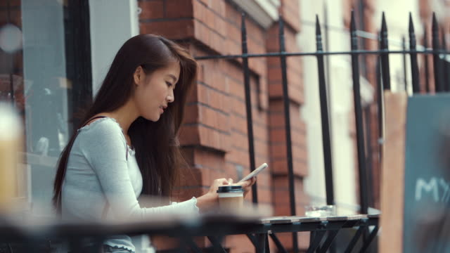 Young Chinese Woman Using Smart Phone in Cafe (slow motion)