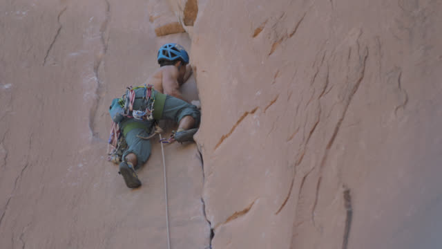 vidéos et rushes de young climber struggles to find a grip on steep sandstone rock face. - lutte concepts
