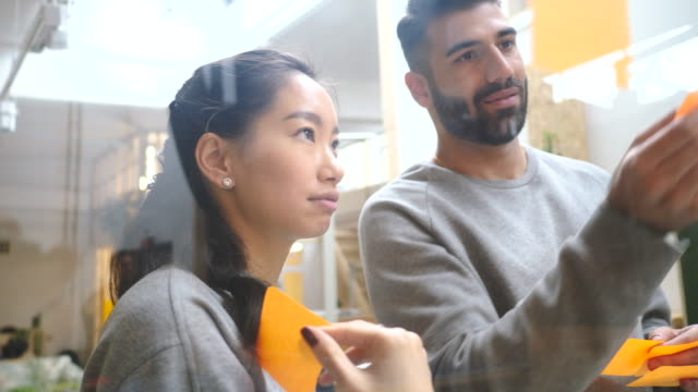 young colleagues discussing business plan while sticking adhesive notes on glass wall in office - adhesive note stock videos & royalty-free footage