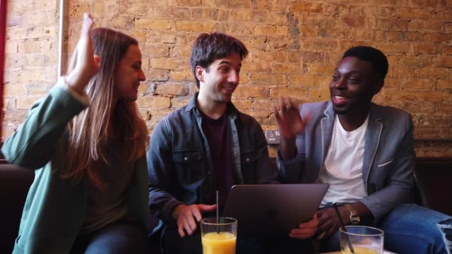 young colleagues working out of the office in a restaurant pub in london, uk - city break stock videos & royalty-free footage