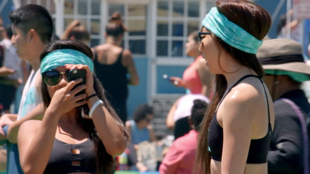 Young college girls having fun after practicing yoga fitness class on Santa Monica Pier in Los Angeles, California, 4K, from RAW file