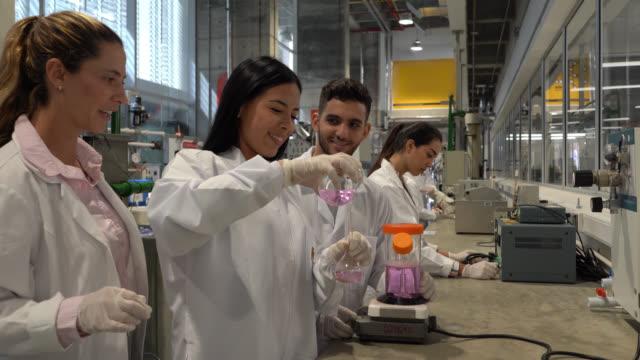 vídeos y material grabado en eventos de stock de jóvenes estudiantes universitarios en una clase de laboratorio de química mezclando líquidos y profesor supervisando muy alegremente - química