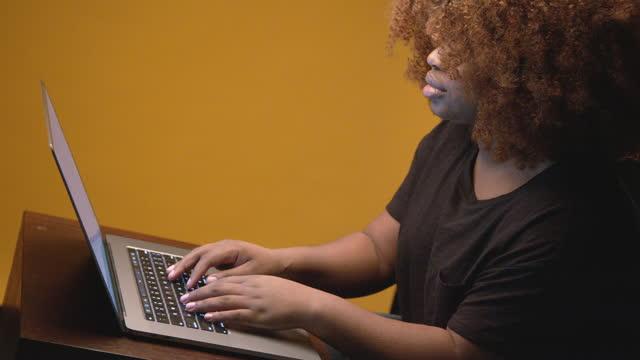 vídeos de stock, filmes e b-roll de jovem, confiante, bonita, mulher afro-americana profissional digitando em um computador portátil como recepcionista, compras online, mensagens nas mídias sociais ou estudo escolar online - coloured background
