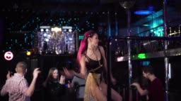 Young confident Caucasian PJ dancing on stage in night club. Portrait of beautiful woman with tattooed hand and red hair working on stage. Lifestyle, occupation, enjoyment.