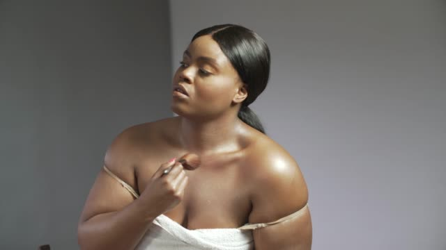 a young confident curvaceous woman applying cream to her neck and shoulders. - wearing a towel stock videos & royalty-free footage