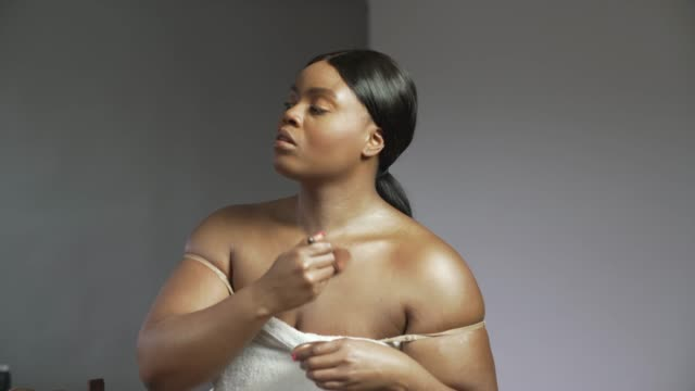 A young confident curvaceous woman applying cream to her neck and shoulders.