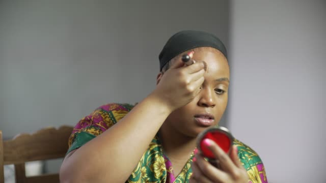 A young confident curvaceous woman applying foundation make-up