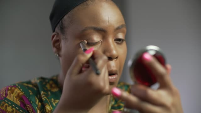 A young confident curvaceous woman applying make-up