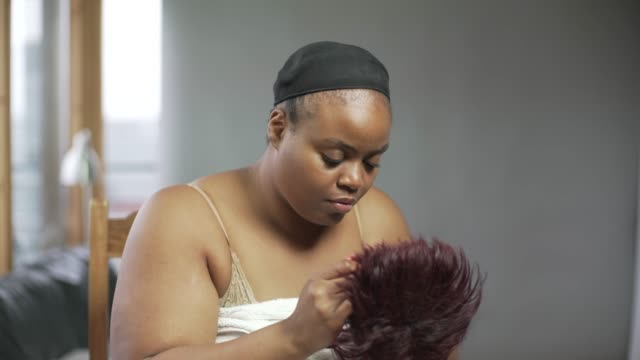 A young confident curvaceous woman putting on a wig.