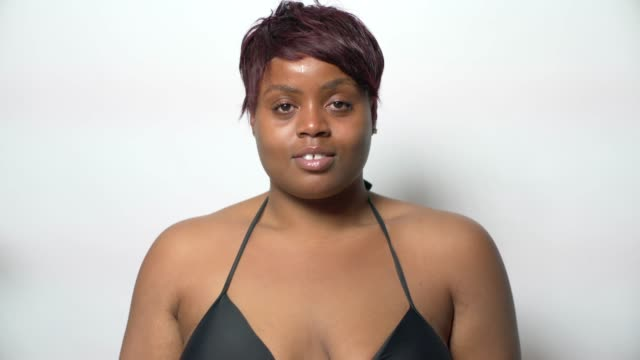 a young confident curvaceous woman wearing a black bikini with no make-up - no make up stock videos & royalty-free footage
