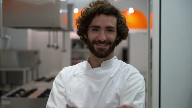 Young confident male chef standing looking at the camera with arms crossed smiling