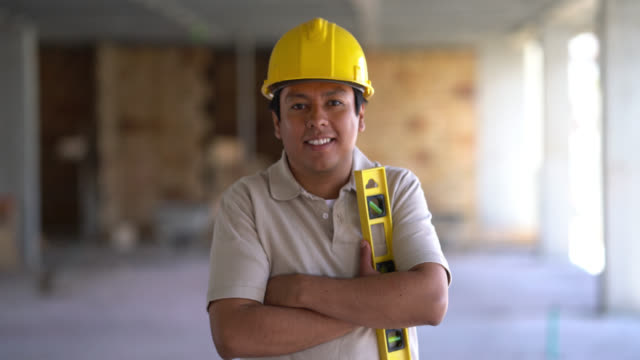 young construction worker looking at the camera smiling with arms crossed - construction worker stock videos and b-roll footage