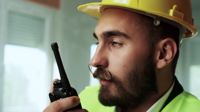 Young construction worker using walkie talkie