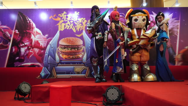 young cosplayers show the game characters for the audience in front of the posters of big mac mcdonald's cooperated with china's hottest egame 'arena... - big mac stock videos and b-roll footage