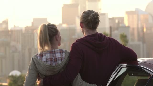 junges paar bewundern blick auf die skyline einer stadt - ankunft stock-videos und b-roll-filmmaterial