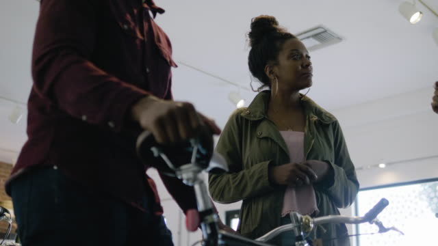 vídeos de stock e filmes b-roll de a young couple admire an urban commuter bike in a bicycle shop, and the store owner assists them - guiador