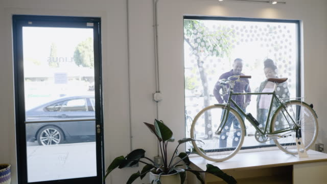 stockvideo's en b-roll-footage met a young couple admire an urban commuting bike in a bicycle shop window - etalage