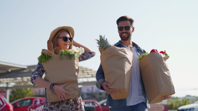 young couple after groceries shopping - paper bag stock videos & royalty-free footage