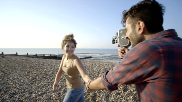 young couple and camcorder on beach - filming stock videos & royalty-free footage