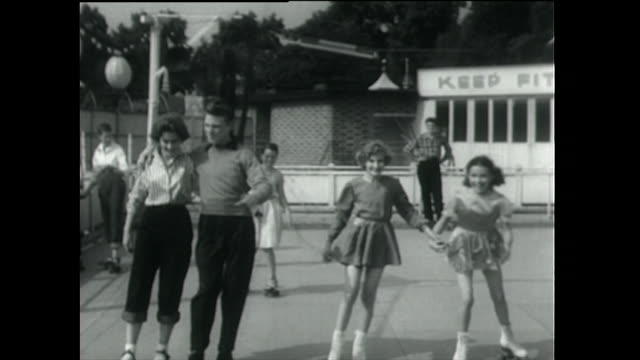 young couple and children rollerskating on outdoor rink; 1955 - showing off stock videos & royalty-free footage