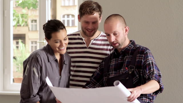 MS Young couple and contractor reviewing blueprints / Berlin, Germany