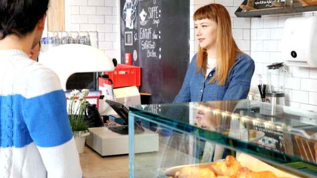 young couple and female barista standing at cafe - display cabinet stock videos & royalty-free footage