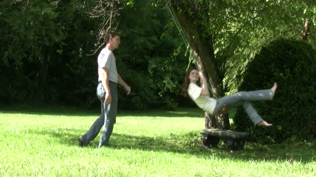 young couple and rope swing 2 - rope swing stock videos & royalty-free footage