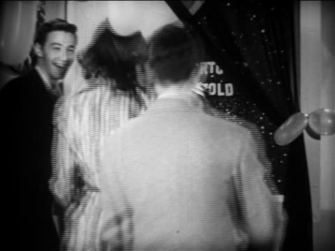 b/w 1949 young couple approach sitting girl dressed as fortune teller looking into crystal ball - teenagerpaar stock-videos und b-roll-filmmaterial