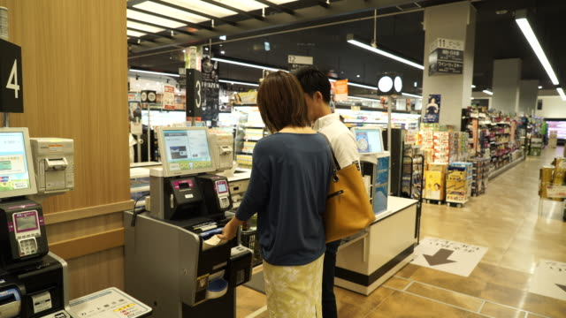 Young couple are settled at the cash register