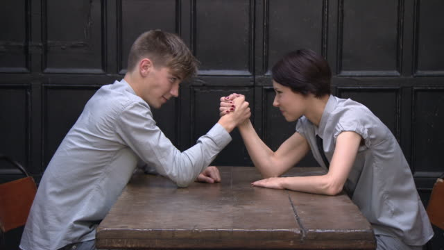 young couple arm wrestling, young woman wins - arm wrestling stock videos & royalty-free footage