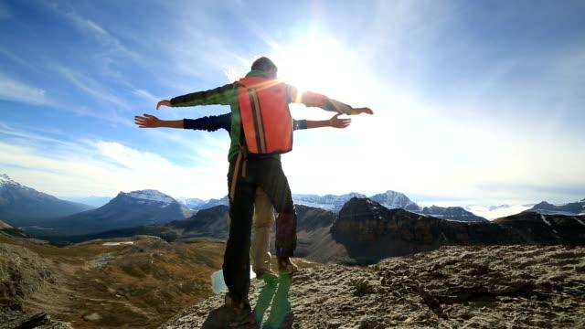 Ungt par armarna utsträckta på bergets topp