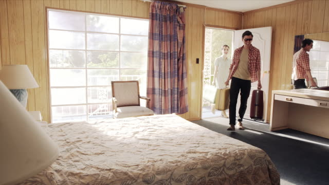 young couple arrive at vegas motel, guys drops luggage and jumps onto bed - ホテル点の映像素材/bロール