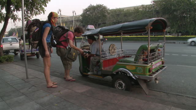 ws zi ms young couple asking for direction to taxi bike driver, bangkok, thailand - 問う点の映像素材/bロール