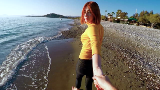 Young couple at 30s walking at the beach with barefoot enjoying the sea,sand and waves. POV III