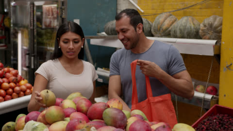 young couple at a farmers market choosing fruits adding them to a reusable bag while talking and smiling - mango fruit stock videos & royalty-free footage