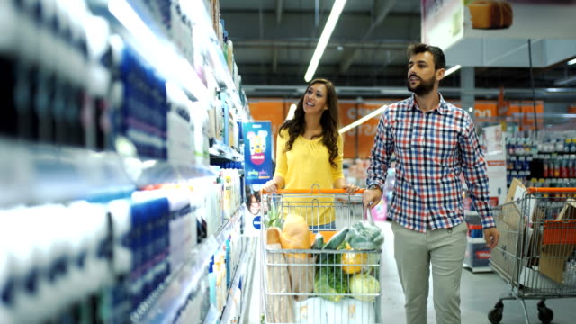 young couple at a supermarket. - body care stock videos & royalty-free footage