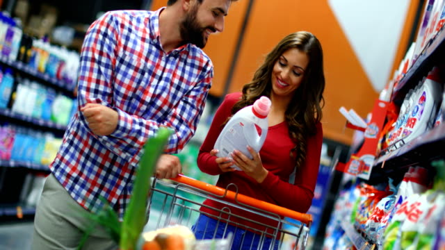 young couple at a supermarket. - laundry detergent stock videos & royalty-free footage