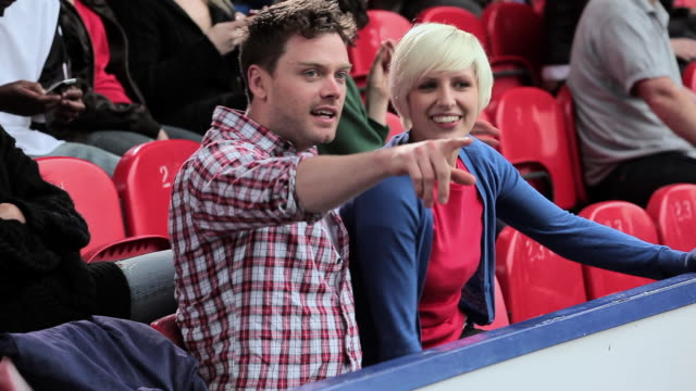 young couple at football match - sitting stock videos & royalty-free footage